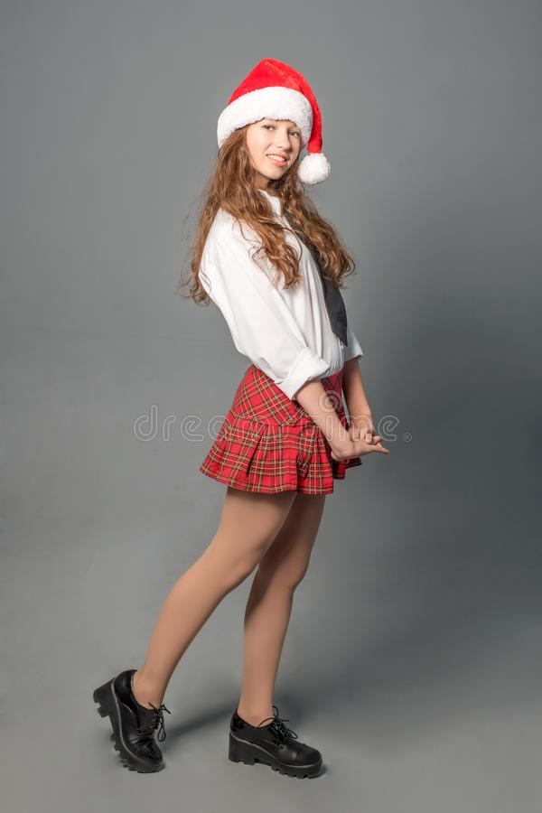 Αρκετά ντροπαλή γυναίκα σπουδαστής σε μια κοντά σχολική στολή και ένα καπέλο Santa στοκ φωτογραφίες