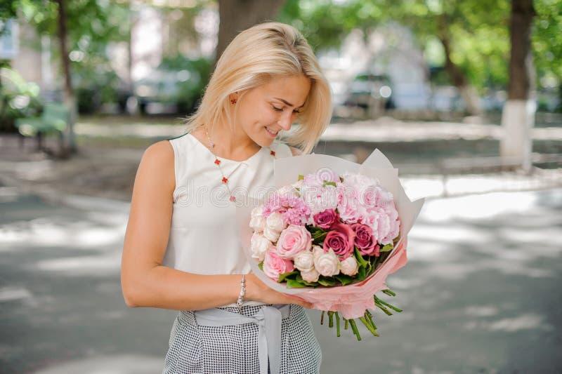 Αρκετά ξανθή γυναίκα που κρατά μια όμορφη σύνθεση των λουλουδιών στοκ εικόνες