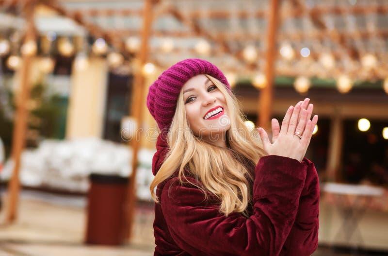 Αρκετά ξανθή γυναίκα που φορά τα θερμά χειμερινά ενδύματα, που θέτουν στο β στοκ φωτογραφία με δικαίωμα ελεύθερης χρήσης