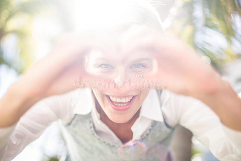 Αρκετά ξανθή γυναίκα που χαμογελά στη κάμερα και που κάνει τη μορφή καρδιών με τα χέρια της στοκ φωτογραφίες με δικαίωμα ελεύθερης χρήσης