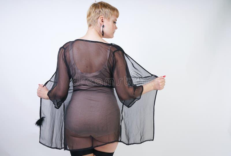 Αρκετά ξανθή κοντή αναδρομική γυναίκα τρίχας με τη curvy τοποθέτηση σωμάτων στο μπεζ εκλεκτής ποιότητας κομπινεζόν και προκλητικέ στοκ φωτογραφίες