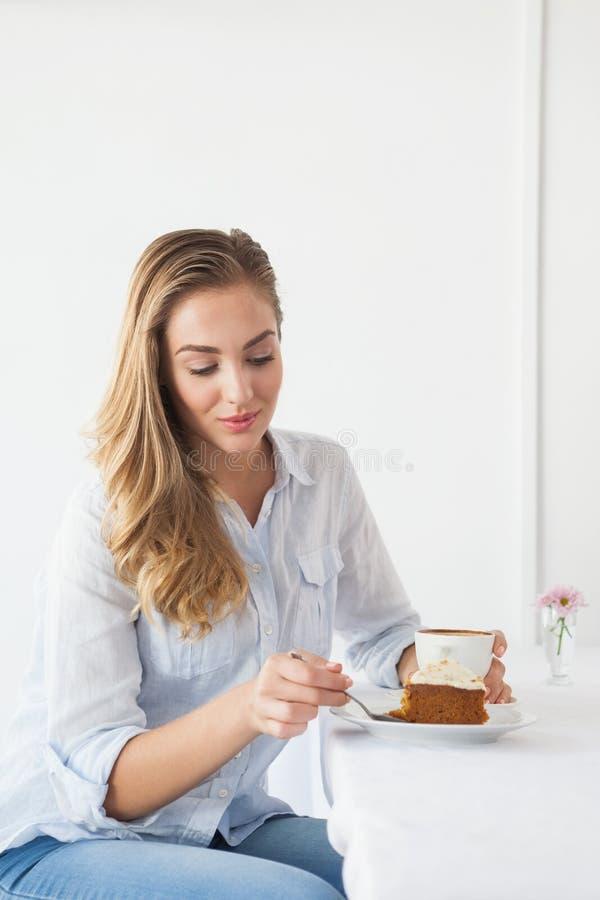 Αρκετά ξανθός έχοντας το κέικ και τον καφέ στοκ φωτογραφία