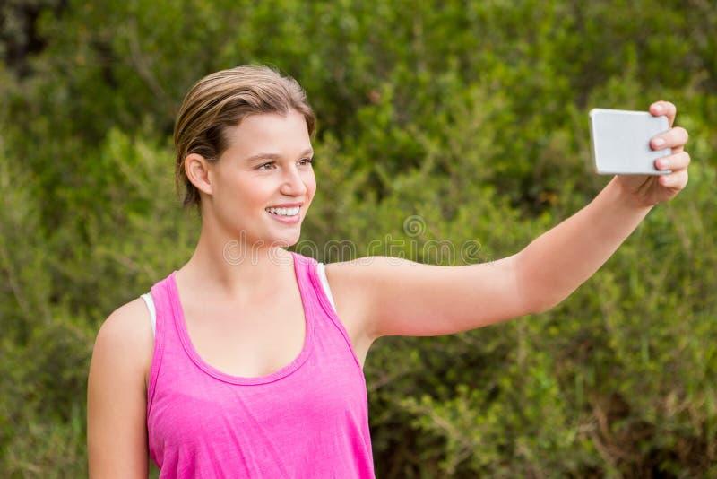 Αρκετά ξανθός αθλητής που χαμογελά και που παίρνει selfies στοκ εικόνα με δικαίωμα ελεύθερης χρήσης