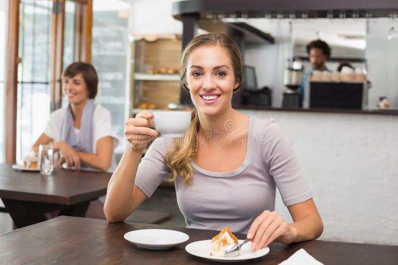 Αρκετά ξανθός απολαμβάνοντας το κέικ και τον καφέ στοκ εικόνες