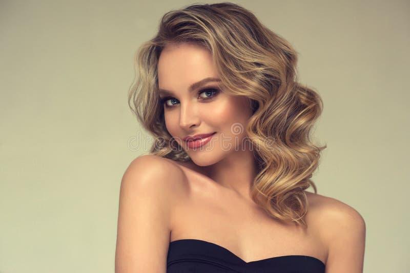 Αρκετά ξανθός-μαλλιαρό πρότυπο με το σγουρό, χαλαρό hairstyle και το ελκυστικό makeup στοκ εικόνες με δικαίωμα ελεύθερης χρήσης