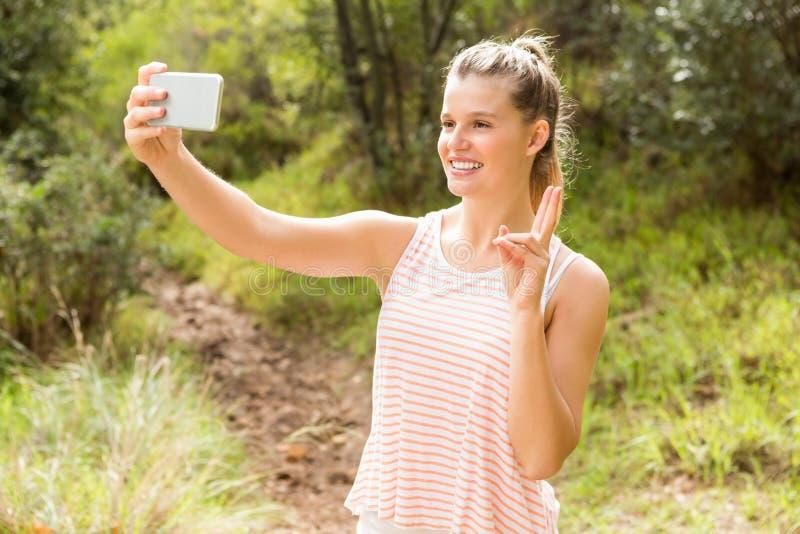 Αρκετά ξανθός παρουσιάζοντας σημάδι ειρήνης και παίρνοντας selfies στοκ φωτογραφίες