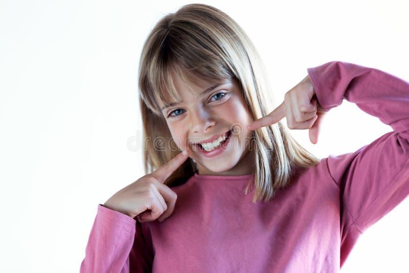 Αρκετά ξανθό μικρό κορίτσι με το τέλειο χαμόγελο που εξετάζει τη κάμερα o στοκ φωτογραφίες με δικαίωμα ελεύθερης χρήσης