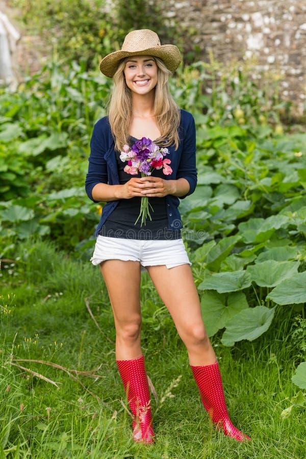 Αρκετά ξανθό χαμόγελο στα λουλούδια εκμετάλλευσης καμερών στοκ φωτογραφίες με δικαίωμα ελεύθερης χρήσης