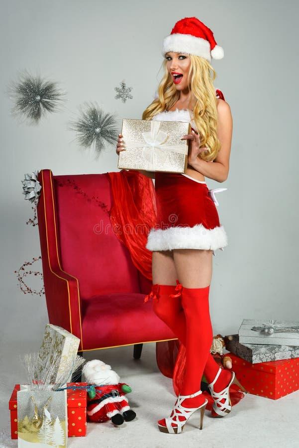 Αρκετά προκλητική γυναίκα με τα μακριά πόδια που φορούν τα ενδύματα Άγιου Βασίλη στοκ φωτογραφία