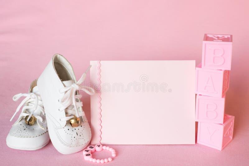 Αρκετά ροζ κάρτα πρόσκλησης ντους κοριτσάκι ή ανακοίνωση γέννησης με τα εκλεκτής ποιότητας άσπρα παπούτσια στο ρόδινο υπόβαθρο υφ στοκ φωτογραφία με δικαίωμα ελεύθερης χρήσης