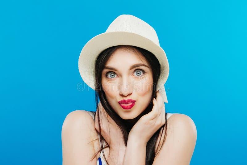 Αρκετά σκοτεινός-μαλλιαρό κορίτσι που φορά την τοποθέτηση θερινών καπέλων στο στούντιο στο μπλε υπόβαθρο στοκ εικόνα με δικαίωμα ελεύθερης χρήσης
