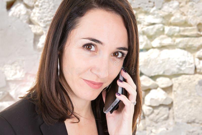 Αρκετά σοβαρή επιχειρησιακή γυναίκα στο τηλέφωνο κάτω από το παλαιό άσπρο υπόβαθρο τοίχων πετρών στοκ εικόνες