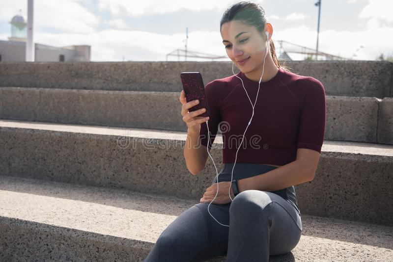 Αρκετά φίλαθλο brunette που εξετάζει το τηλέφωνο στοκ εικόνες