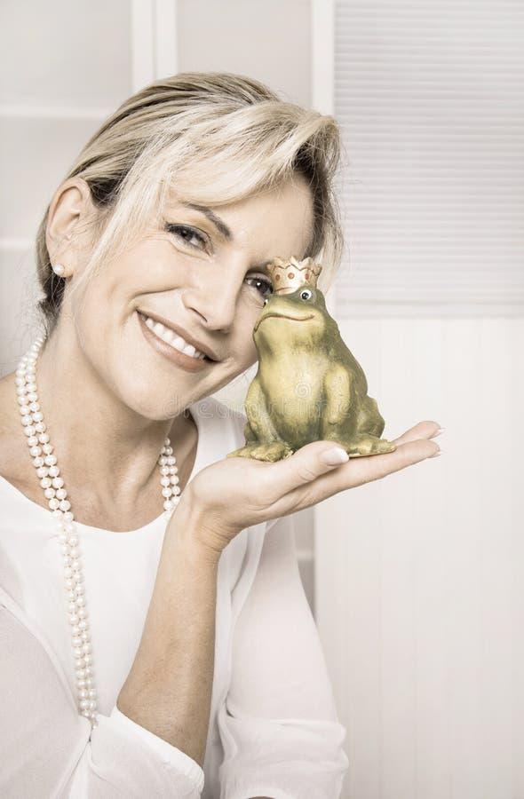 Αρκετά χαμογελώντας ηλικιωμένη γυναίκα με έναν πράσινο βάτραχο στα χέρια της Conce στοκ φωτογραφίες