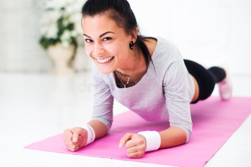 Αρκετά χαμογελώντας νέα γυναίκα που κάνει τη σανίδα κοιλιακή στοκ εικόνες με δικαίωμα ελεύθερης χρήσης
