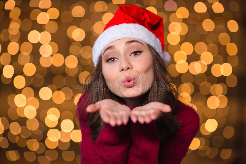 Αρκετά χαριτωμένο σγουρό κορίτσι στο καπέλο Άγιου Βασίλη που στέλνει τα φιλιά στοκ εικόνα