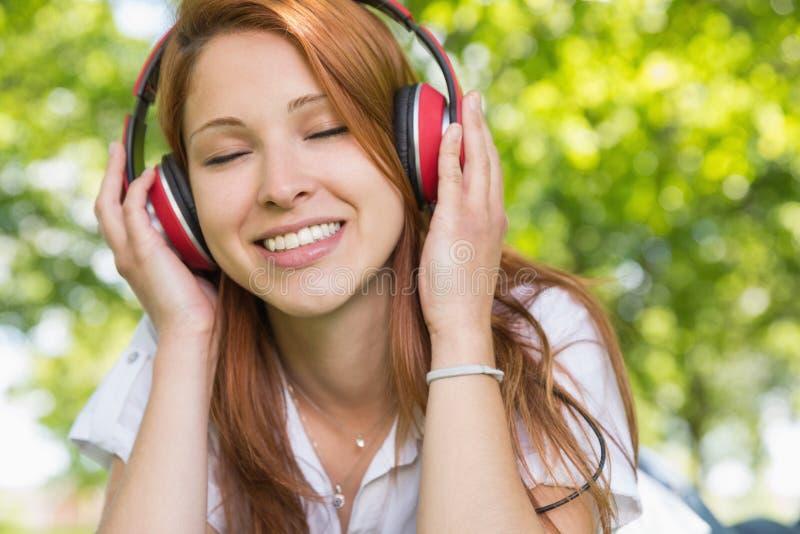 Αρκετά redhead άκουσμα τη μουσική στο πάρκο στοκ εικόνες με δικαίωμα ελεύθερης χρήσης