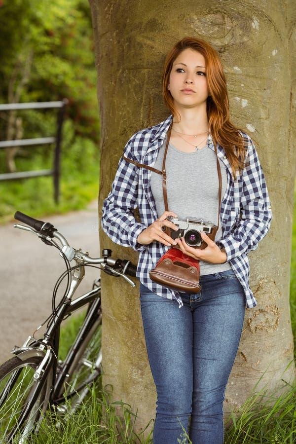 Αρκετά redhead εκμετάλλευση η κάμερα της που κλίνει ενάντια σε ένα δέντρο στοκ φωτογραφία με δικαίωμα ελεύθερης χρήσης