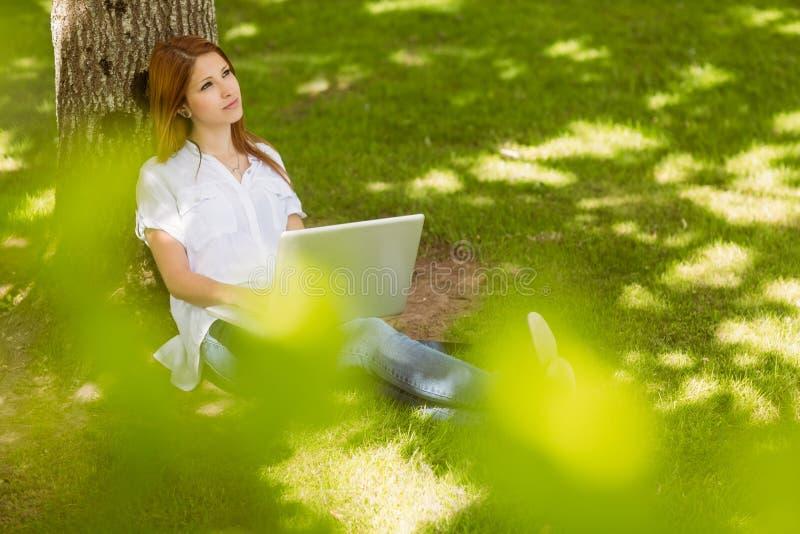 Αρκετά redhead συνεδρίαση ενάντια σε έναν κορμό με το lap-top της στοκ εικόνα