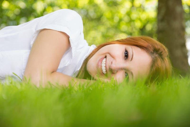 Αρκετά redhead χαμόγελο στη κάμερα που βρίσκεται στη χλόη στοκ εικόνες
