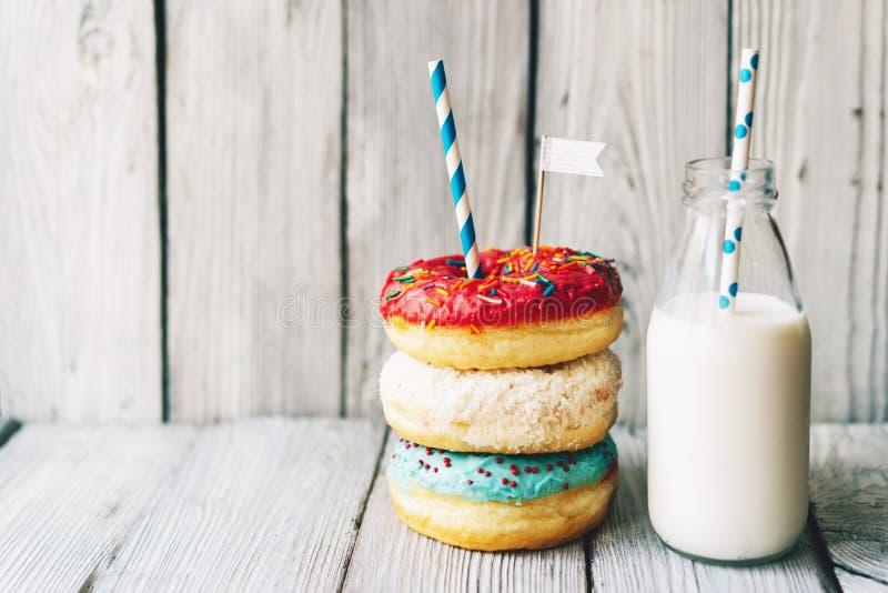 Αρκετοί βερνίκωσαν την κρέμα donuts και το γάλα σε ένα μπουκάλι στοκ φωτογραφία