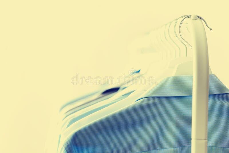 Αρσενικά ενδύματα, σακάκια και πουκάμισα που κρεμούν στη ράγα ενδυμάτων Μπλε ενδύματα χρώματος διάστημα αντιγράφων Εικόνα με την  στοκ εικόνες με δικαίωμα ελεύθερης χρήσης