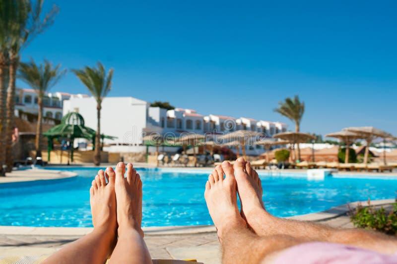 Αρσενικά και θηλυκά πόδια στο υπόβαθρο της λίμνης στο ξενοδοχείο στοκ φωτογραφίες