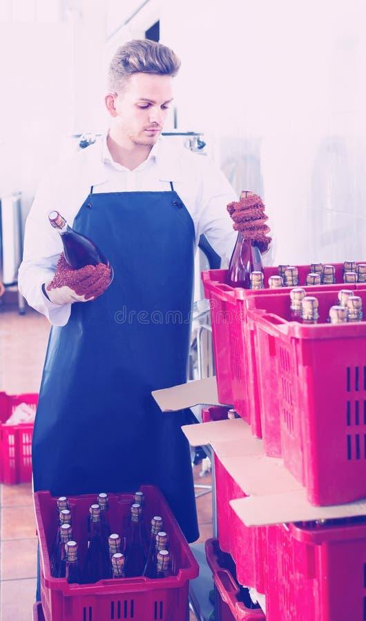 Αρσενικά μπουκάλια κρασιού συσκευασίας υπαλλήλων στο εργοστάσιο λαμπιρίζοντας κρασιού στοκ εικόνες με δικαίωμα ελεύθερης χρήσης
