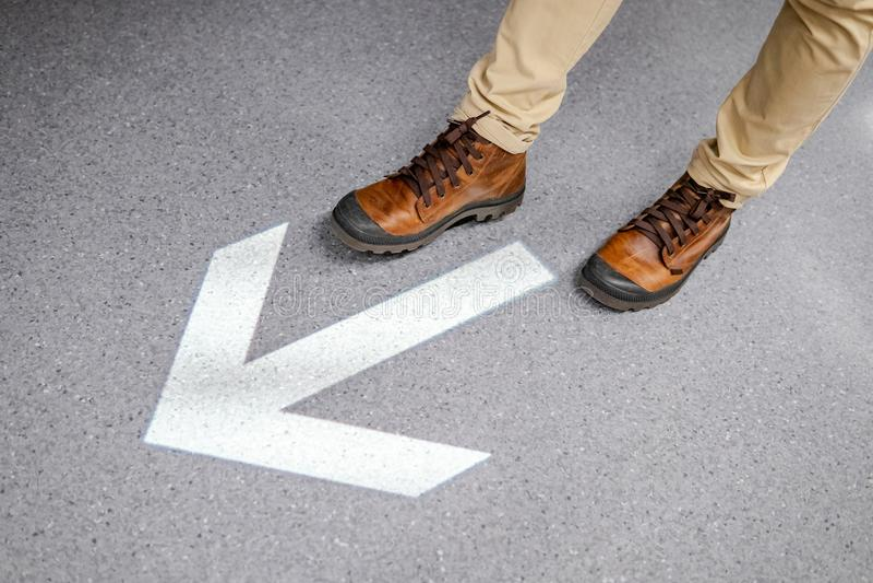 Αρσενικά πόδια που περπατούν πέρα από arrowhead το σημάδι στο πάτωμα στοκ φωτογραφίες