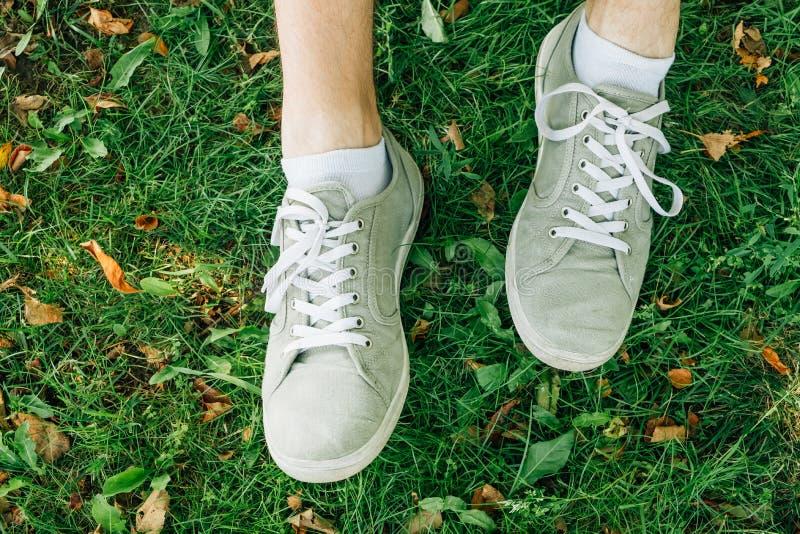Αρσενικά πόδια στα γκρίζα gumshoes στη χλόη στοκ εικόνες με δικαίωμα ελεύθερης χρήσης