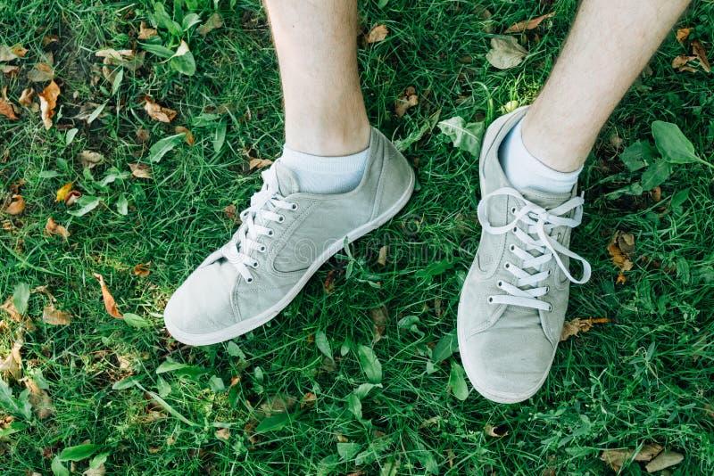 Αρσενικά πόδια στα γκρίζα gumshoes στη χλόη στοκ εικόνες