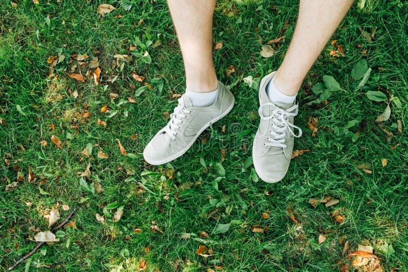 Αρσενικά πόδια στα γκρίζα gumshoes στη χλόη στοκ φωτογραφία με δικαίωμα ελεύθερης χρήσης