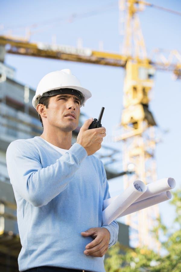 Αρσενικά σχεδιαγράμματα εκμετάλλευσης αρχιτεκτόνων χρησιμοποιώντας walkie-talkie στο εργοτάξιο οικοδομής στοκ εικόνες με δικαίωμα ελεύθερης χρήσης