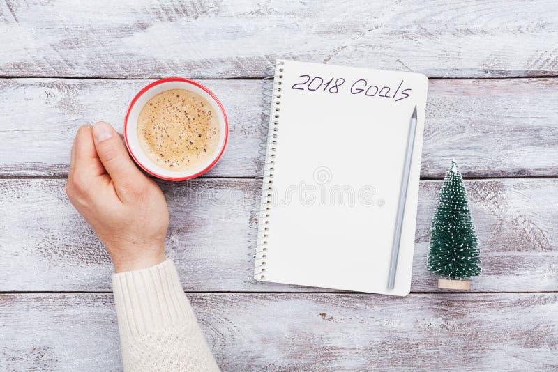 Αρσενικά φλιτζάνι του καφέ και σημειωματάριο λαβής χεριών με τους στόχους για το 2018 Προγραμματισμός και κίνητρο για τη νέα έννο στοκ φωτογραφία με δικαίωμα ελεύθερης χρήσης