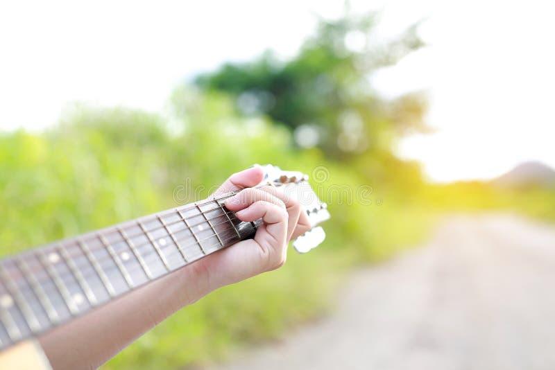 Αρσενικά χέρια κινηματογραφήσεων σε πρώτο πλάνο που παίζουν στην ακουστική κιθάρα στη φύση στοκ εικόνα με δικαίωμα ελεύθερης χρήσης