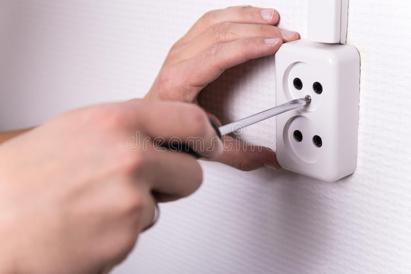 Αρσενικά χέρια με το κατσαβίδι που εγκαθιστά την ηλεκτρική υποδοχή στον τοίχο στοκ εικόνα με δικαίωμα ελεύθερης χρήσης