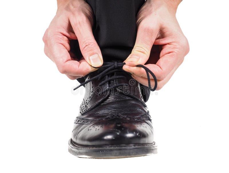 Αρσενικά χέρια που δένουν τα κορδόνια στα μαύρα παπούτσια δέρματος στοκ εικόνες