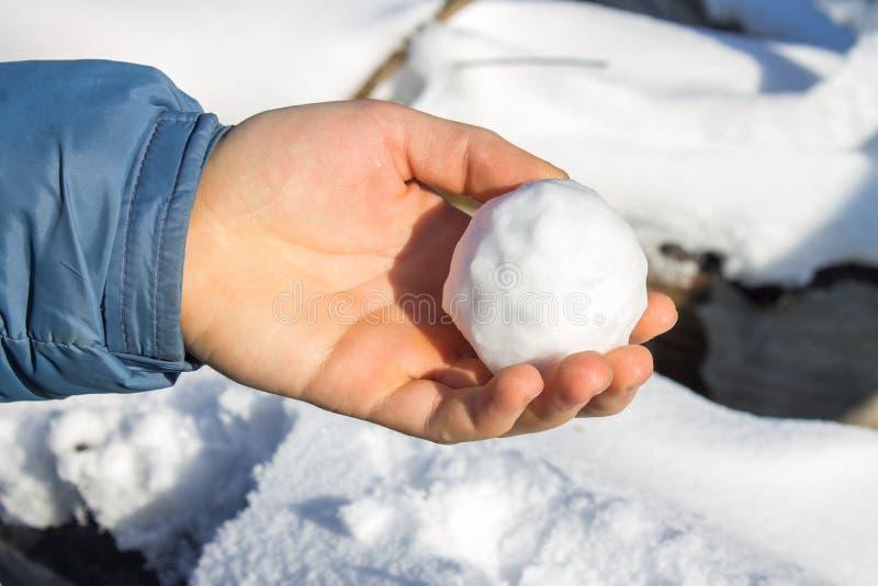 Αρσενικά χέρια που από τις μικρές χιονιές χιονιού που θα έκαναν έναν χιονάνθρωπο στοκ φωτογραφία