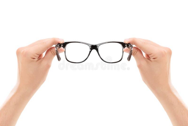 Αρσενικά χέρια που κρατούν ένα ζευγάρι των γυαλιών στοκ εικόνα