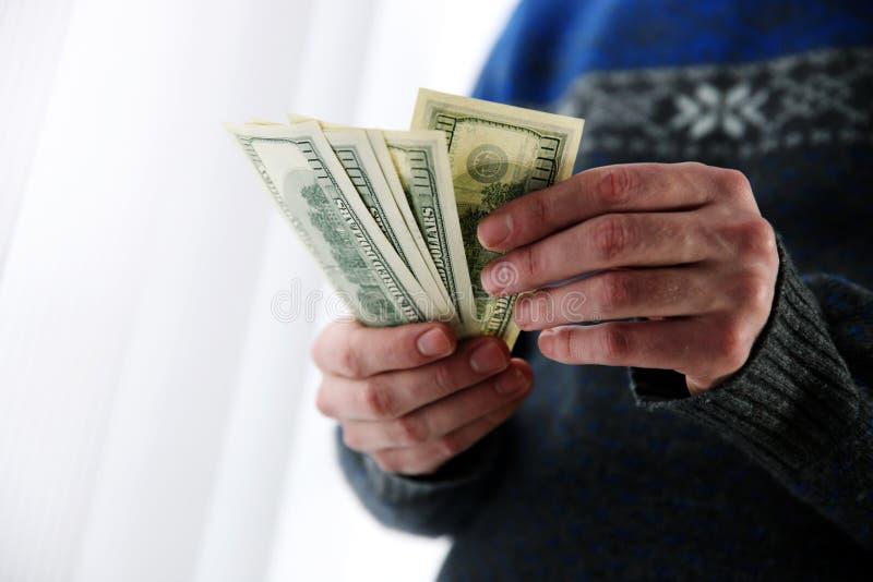 Αρσενικά χέρια που κρατούν τα αμερικανικά δολάρια στοκ εικόνες