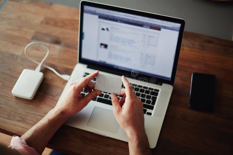 Αρσενικά χέρια που κρατούν την πιστωτική κάρτα που χρησιμοποιεί το lap-top στο σπίτι στοκ εικόνα
