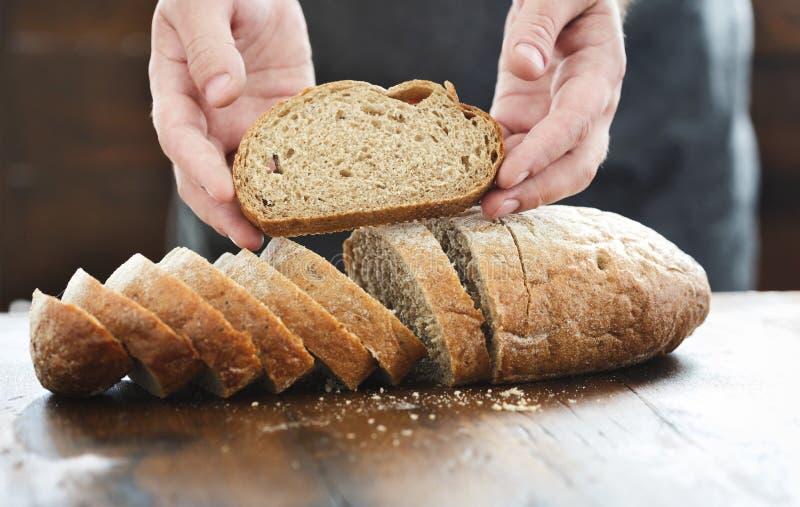 Αρσενικά χέρια που κρατούν τον ξύλινο πίνακα ψωμιού φετών στοκ εικόνες