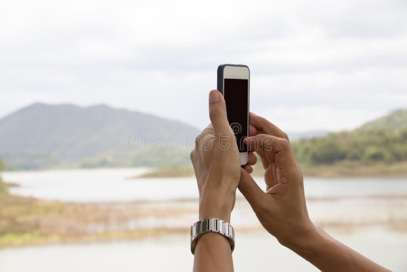 Αρσενικά χέρια που κρατούν το έξυπνο τηλέφωνο, που παίρνει την εικόνα λιμνών στοκ φωτογραφία με δικαίωμα ελεύθερης χρήσης