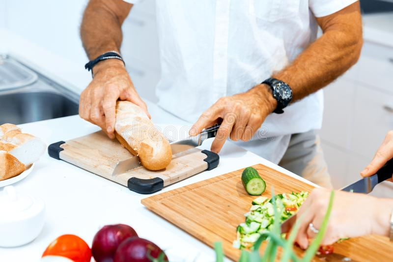 Αρσενικά χέρια που κόβουν το ψωμί στοκ εικόνες