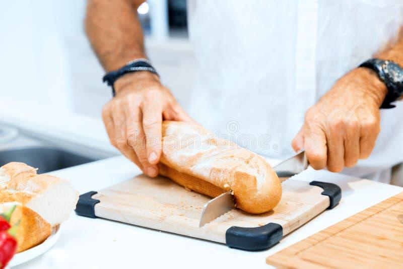 Αρσενικά χέρια που κόβουν το ψωμί στοκ φωτογραφία