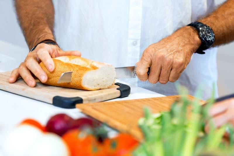 Αρσενικά χέρια που κόβουν το ψωμί στοκ φωτογραφίες με δικαίωμα ελεύθερης χρήσης