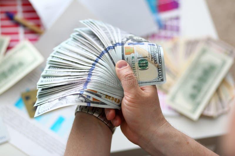 Αρσενικά χέρια που μετρούν τα χρήματα από το τεράστιο πακέτο στοκ φωτογραφία