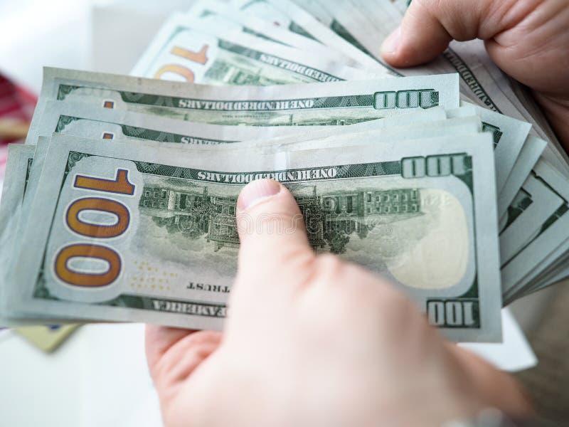 Αρσενικά χέρια που μετρούν τους λογαριασμούς αμερικανικών εκατό bucks στοκ εικόνες