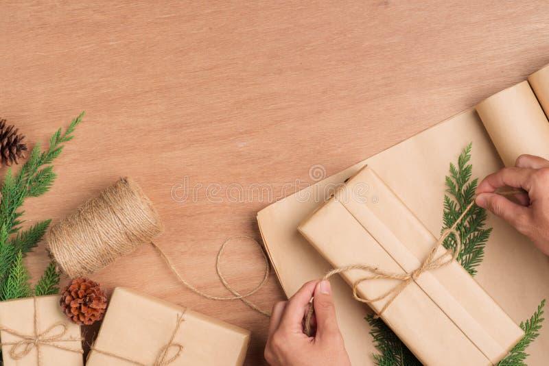 Αρσενικά χέρια που τυλίγουν τα δώρα Χριστουγέννων στο έγγραφο και που εμπλέκουν τα στο W στοκ εικόνες