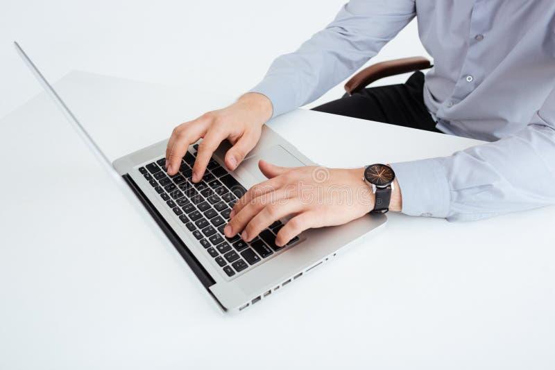 Αρσενικά χέρια που χρησιμοποιούν το φορητό προσωπικό υπολογιστή στην αρχή στοκ εικόνες